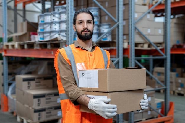 Portret zadowolony przystojny mieszańca rasy w kamizelce odblaskowej niosący zapakowane towary podczas przygotowywania go do wysyłki