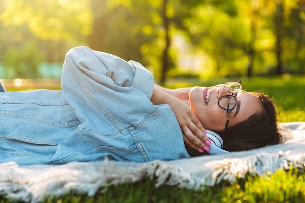 Portret zadowolony uśmiechnięta śliczna młoda studentka nosząca okulary na zewnątrz w parku przyrody słuchając muzyki ze słuchawkami leży na trawie.