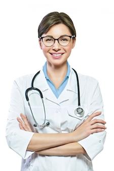 Portret zadowolony uśmiechnięty lekarz w białym mundurze stojącym ze skrzyżowanymi rękami na białym tle