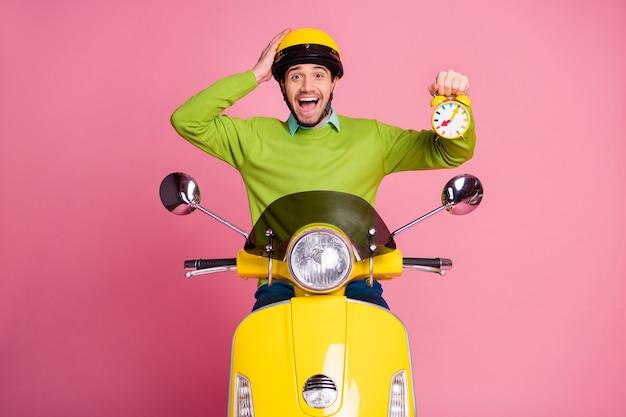 Portret zadowolony wesoły facet jedzie motorowerem trzymając w ręku zegar