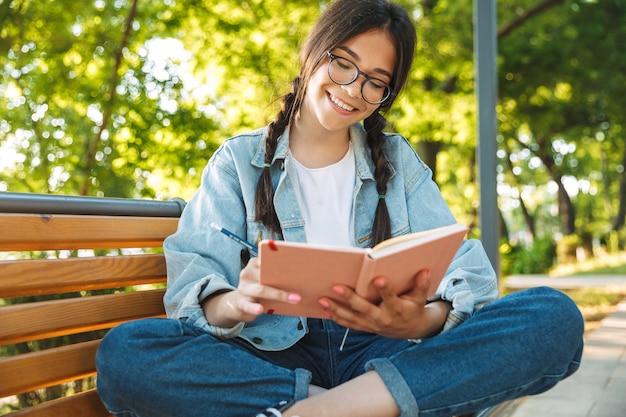 Portret zadowolony wesoły ładny młody student dziewczyna nosi okulary, siedząc na ławce na zewnątrz w parku przyrody, pisanie notatek w notesie.