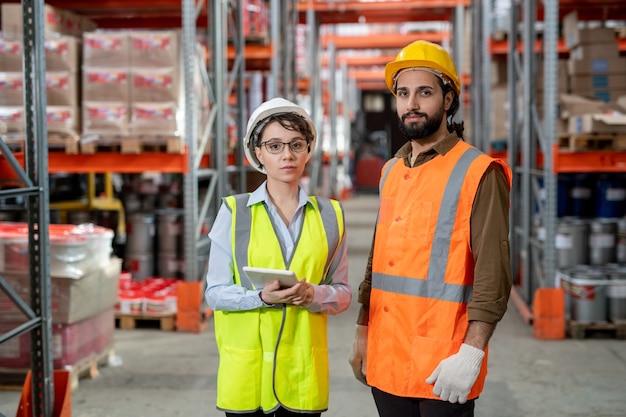 Portret zadowolonych młodych pracowników w kamizelkach odblaskowych i kaskach stojących w przejściu do magazynu