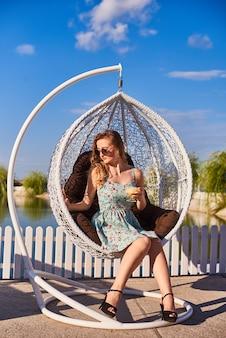 Portret zadumana kobieta siedzi w białym wiszącym rattanowym krześle w okularach przeciwsłonecznych