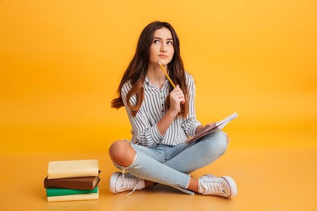 Portret zadumana młoda dziewczyna robi notatkom