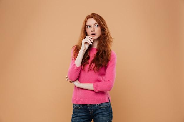 Portret zadumana młoda rudzielec dziewczyna patrzeje daleko od