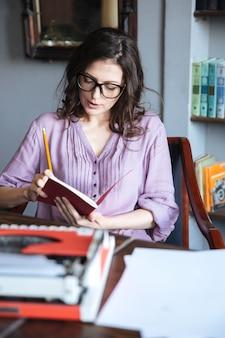 Portret zadumanej dojrzałej autorki w okularach