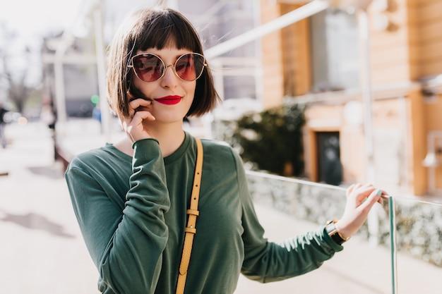 Portret zainteresowanej białej dziewczyny z krótkimi włosami pozuje w ciemnych okularach przeciwsłonecznych. zewnątrz zdjęcie błogiej stylowej kobiety w zielonym swetrze chłodzenie w weekend.