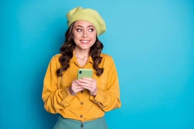 Portret zainteresowanej dziewczyny używa smartfona podążaj za komentarzem udostępnij wiadomości w sieci społecznościowej wygląd copyspace nosić żółtą koszulę na białym tle nad niebieskim kolorem tła