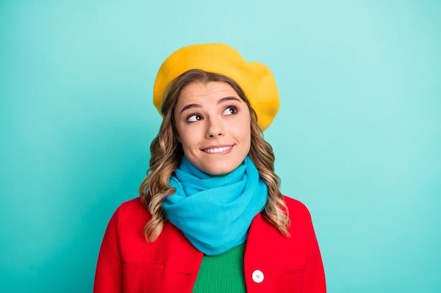 Portret zainteresowanej pozytywnej dziewczyny, która wygląda na copyspace, myślę, że myśli sobie wyobrazić jej walentynkowy prezent zgryz zęby usta noszą zielony sweter na białym tle nad turkusowym kolorem tła