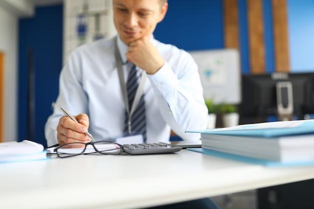 Portret zajęty człowiek siedzi na krześle. poważny pracownik biurowy przygotowuje miesięczny raport. zawodowy księgowy w gabinecie. udana koncepcja firmy finansowej i gospodarki