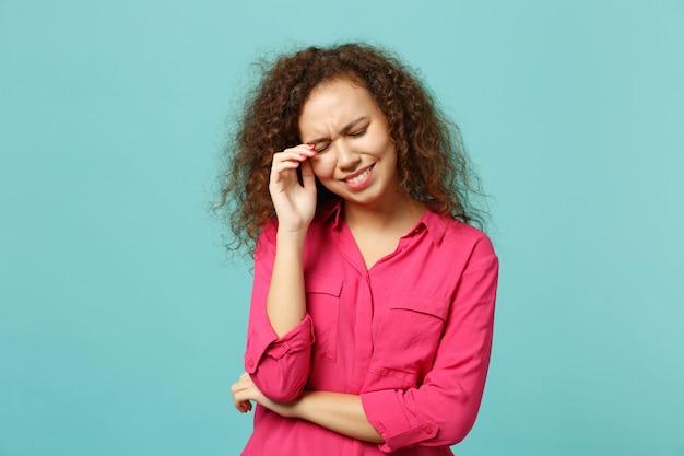 Portret zakłopotany nerwowy afrykański dziewczyna w ubraniu płacz, ocierając łzy na białym tle na tle niebieskiej ściany turkus w studio. koncepcja życia szczere emocje ludzi. makieta miejsca na kopię.