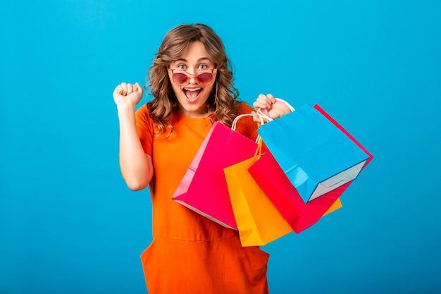 Portret zakupoholiczka podekscytowana atrakcyjna uśmiechnięta stylowa kobieta w pomarańczowej modnej sukience trzymając torby na zakupy na niebieskim tle studio na białym tle