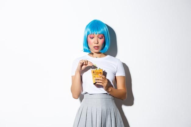 Portret zalotnej azjatki w niebieskiej peruce świętującej halloween, jedzącej słodycze z torby trick or treat, stojąc.