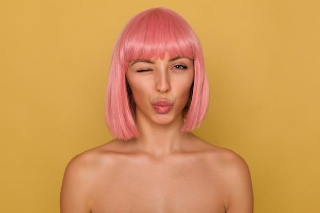 Portret zalotnej ładnej młodej kobiety z różową fryzurą bob, wydymając usta w pocałunku w powietrzu i mrugając, patrząc pozytywnie na kamerę, pozując nad musztardową ścianą