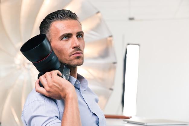 Portret zamyślonego fotografa trzymającego aparat w studio