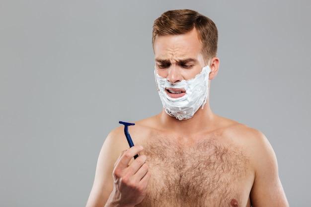 Portret zamyślonego mężczyzny przed goleniem na szarej ścianie