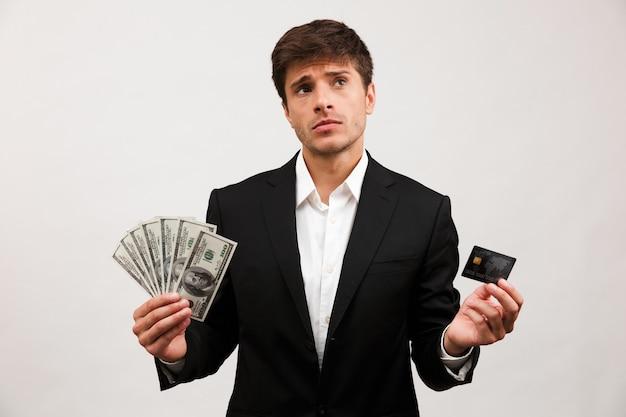 Portret zamyślonego młodego biznesmena stojącego
