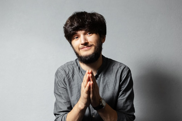 Portret zamyślonego młodego brodatego faceta z rozczochranymi włosami, trzyma dłonie w geście modlitwy na szarym.