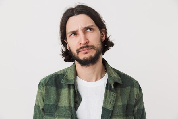 Portret zamyślonego młodego brodatego mężczyzny w zwykłych ubraniach, stojącego na białym tle nad ścianą, odwracającego wzrok
