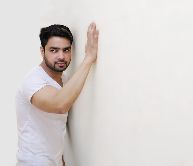 Portret zamyślonego młodego przystojnego indyjskiego mężczyzny na tle białej ściany