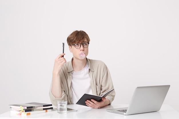 Portret zamyślonego młodzieńca nosi beżową koszulę i okulary, myśląc i dmuchając bąbelki gumą do żucia przy stole z laptopem i notebookami odizolowanymi na białej ścianie