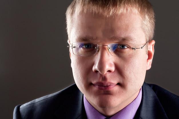Portret zamyślonego, odnoszącego sukcesy biznesmena w okularach