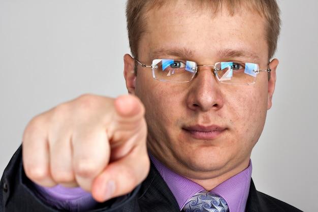 Portret zamyślonego, odnoszącego sukcesy biznesmena, wskazującego na ciebie
