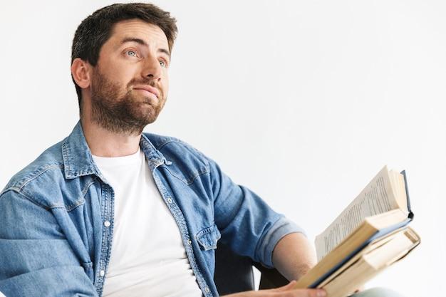 Portret zamyślonego, przystojnego brodatego mężczyzny w zwykłych ubraniach, siedzącego na krześle na białym tle nad białą ścianą, trzymającego książki