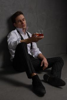 Portret zamyślonego przystojnego młodzieńca ze szklanką alkoholu w dłoniach siedzącego na piętrze