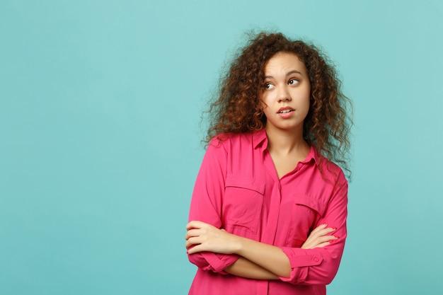 Portret zamyślonej afrykańskiej dziewczyny w różowe ubranie, patrząc na bok, trzymając się za ręce skrzyżowane na białym tle na tle niebieskiej ściany turkus. ludzie szczere emocje, koncepcja stylu życia. makieta miejsca na kopię.