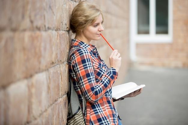 Portret zamyślonej dziewczynka studenta przeciwko mur ceglany, marzy