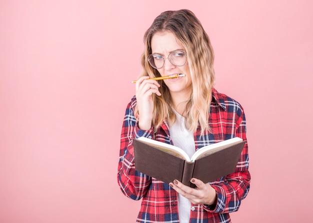 Portret zamyślonej dziewczyny w kraciastej koszuli z notatnikiem i ołówkiem w ustach. pojedynczo na różowej ścianie z miejsca na kopię.