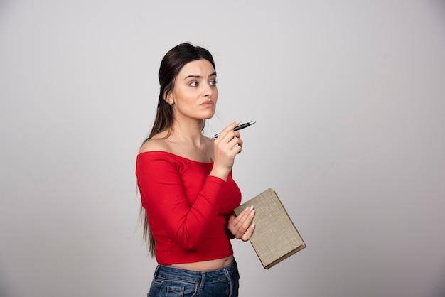 Portret zamyślonej kobiety trzymającej książkę.