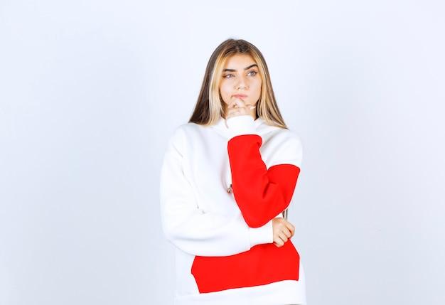 Portret zamyślonej kobiety w ciepłej bluzie z kapturem, stojącej i myślącej