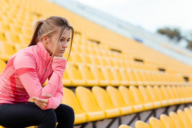 Portret zamyślonej kobiety w sportowej odzieży odpoczynku na stadionie
