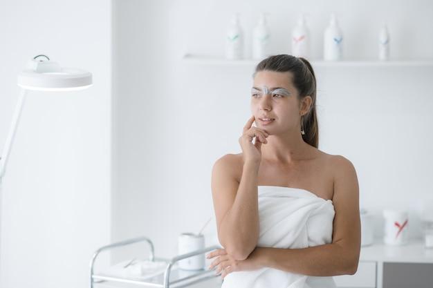 Portret zamyślonej kobiety z woskiem w pobliżu brwi