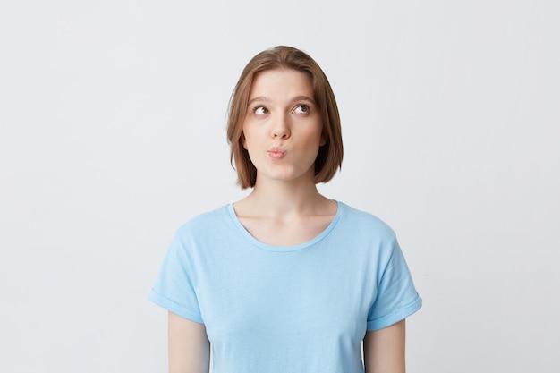 Portret zamyślonej ładnej młodej kobiety w niebieskiej koszulce myśli i czuje się zdziwiony