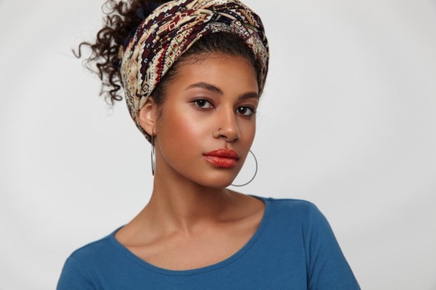 Portret zamyślonej młodej atrakcyjnej, kręconej brunetki kobiety z kolczykiem w nosie, patrząc uważnie na aparat i trzymając usta złożone, stojąc na białym tle