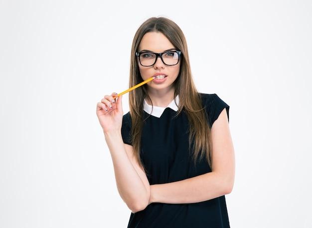 Portret zamyślonej młodej dziewczyny trzymającej ołówek na białym tle