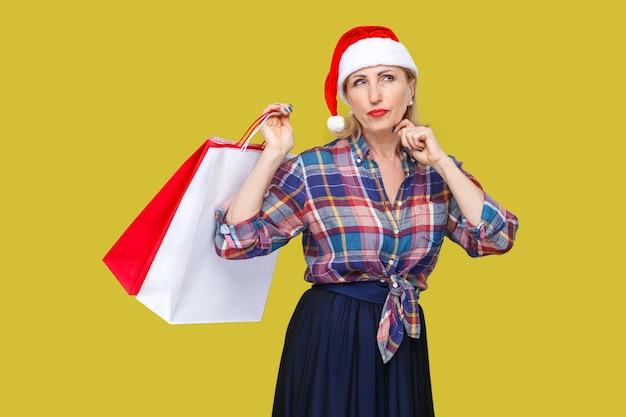 Portret zamyślonej nowoczesnej kobiety w średnim wieku w czerwonej czapce mikołaja i stojącej koszuli w kratkę, trzymającej torby na zakupy z zamyśloną miną, patrząc na kamerę. wewnątrz, strzał studyjny, żółte tło