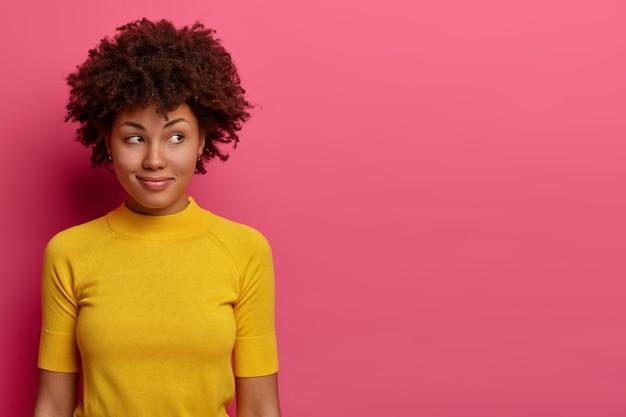 Portret zamyślonej, rozmarzonej kobiety ma delikatny uśmiech, spogląda na bok, myśli nad czymś, nosi niezobowiązującą żółtą koszulkę, zadowolona z przyjemnych myśli, pozuje na różowej ścianie, poza pustą przestrzenią