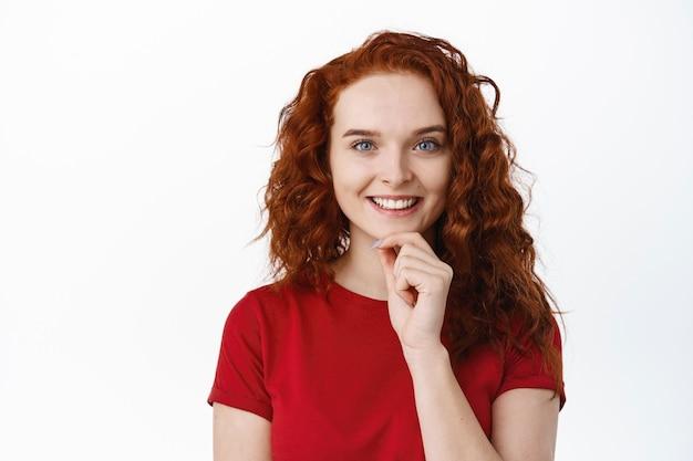 Portret zamyślonej rudowłosej modelki z naturalnym makijażem, dotykającą podbródka i wyglądającą na zamyśloną, myślącą o czymś, biała ściana