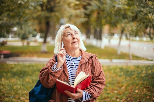 Portret zamyślonej skoncentrowanej starszej kobiety posiadającej notatnik i długopis
