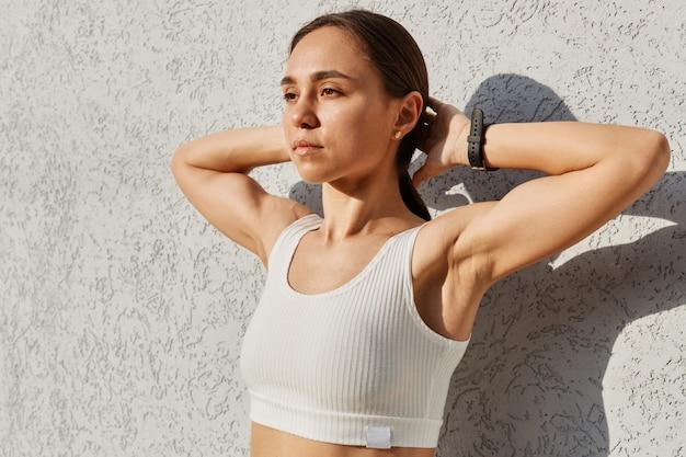 Portret zamyślonej sportowej kobiety o ciemnych włosach, ubrana w biały top, trzymająca ręce za głową, odwracająca wzrok, pozująca po treningu na świeżym powietrzu, zdrowy styl życia.