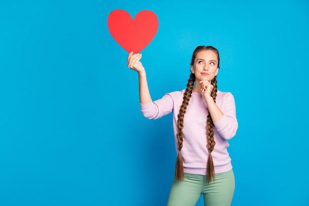 Portret zamyślonej zainteresowanej dziewczyny młodzieżowej z długimi warkoczykami trzymaj czerwoną kartkę papierową prezent w kształcie serca na walentynki pomyśl o randce amora nosić różowy sweter zielone spodnie na białym tle niebieski kolor tło