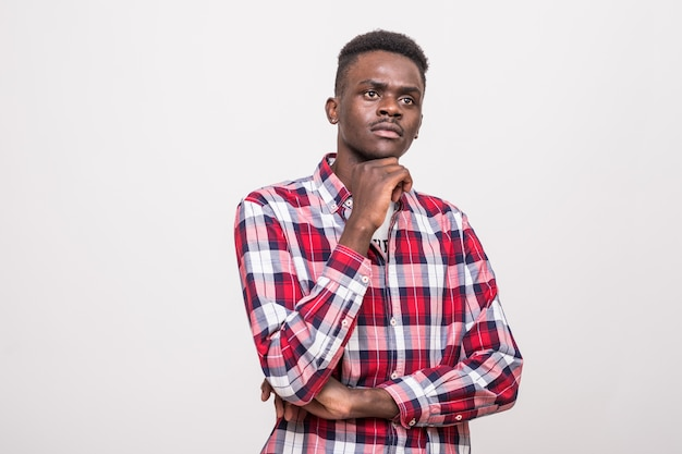 Portret zamyślony afro amerykański mężczyzna stojący z ręką na brodzie i odwracając na białym tle