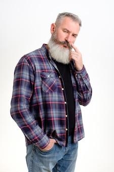 Portret zamyślony dojrzały brodaty mężczyzna ubrany w dżinsy i koszulę w kratę