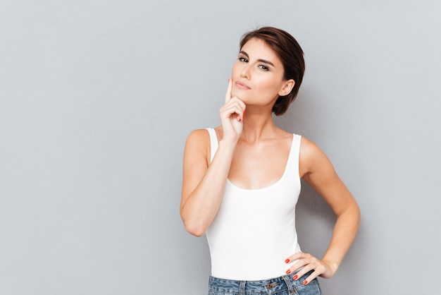 Portret zamyślony ładna dziewczyna myśli o czymś na białym tle na szarym tle