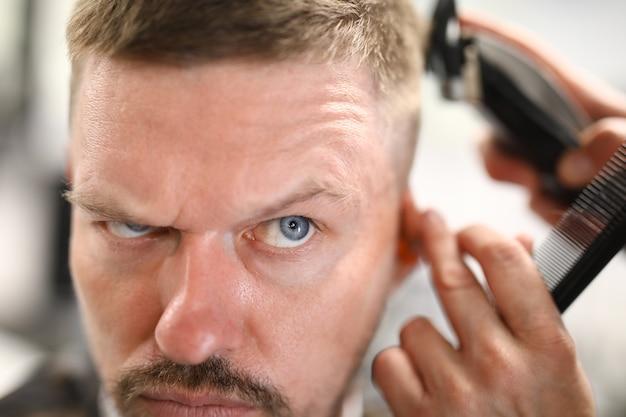 Portret zamyślony mężczyzna, który jest cięty maszyną