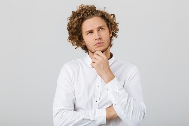 Portret zamyślony młody człowiek z kręconymi włosami